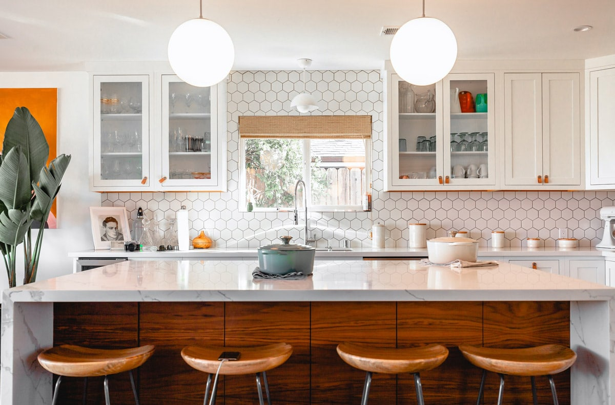 TMDC Group-Construction and Renovation - Photo of a model kitchen with hexagon tile backsplash and Pot filler